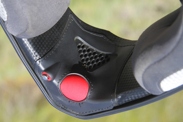 The large red button is the pump at the bottom of the chin bar. The smaller metal button is the pressure release for when you take the helmet off.