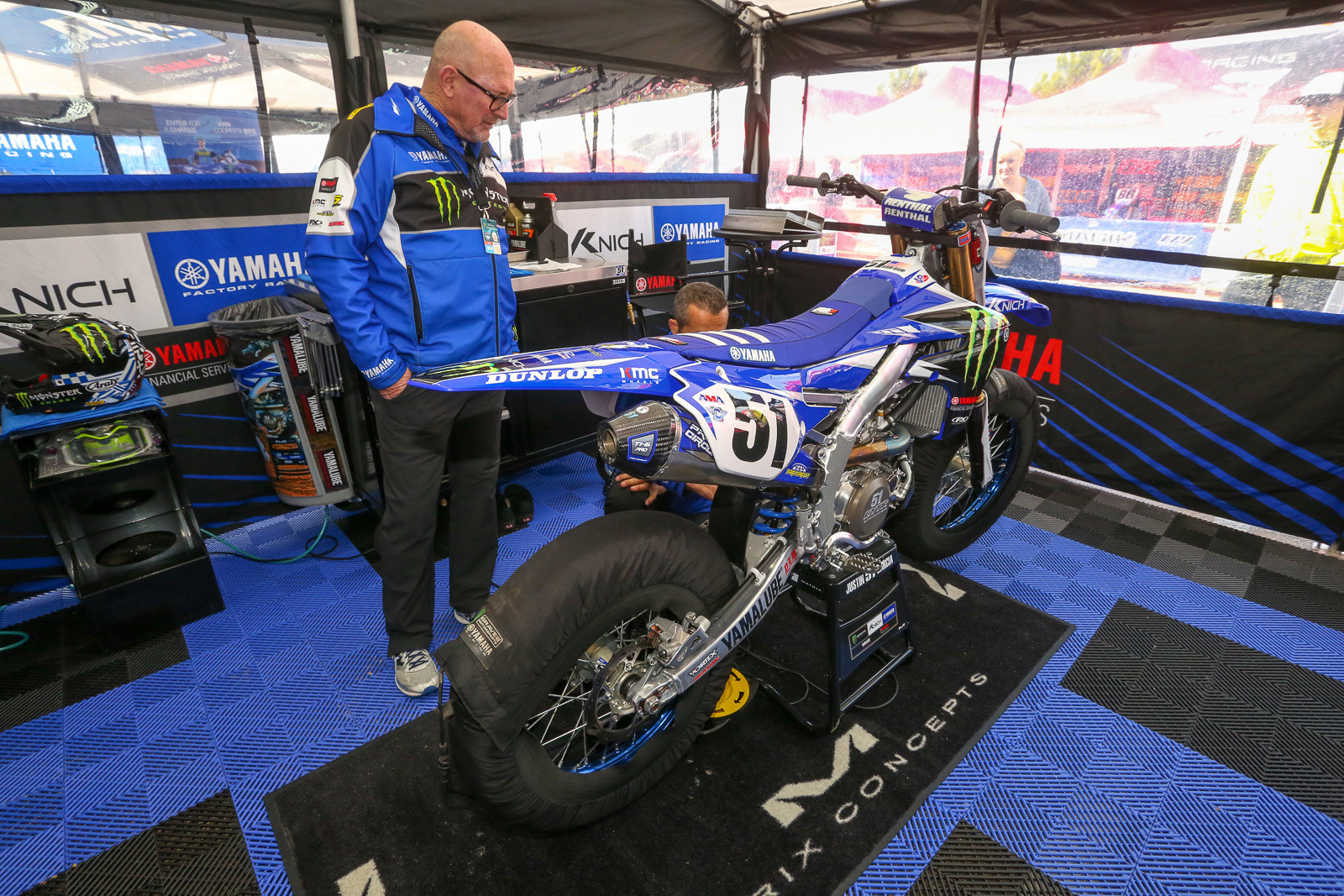 Bob Oliver eyeing up Justin Barcia's YZ450F. The morning started off cool and wet here, and Justin's bike was fitted up with tire warmers.
