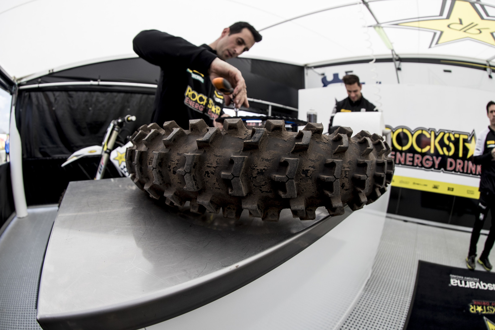 We'll be looking at a lot of the sand tires from this round. Here, under the Rockstar Energy Husqvarna tent, you can see a prototype sand tire from Dunlop. This isn't an MX11 or MX12, their currently available MX sand tires.