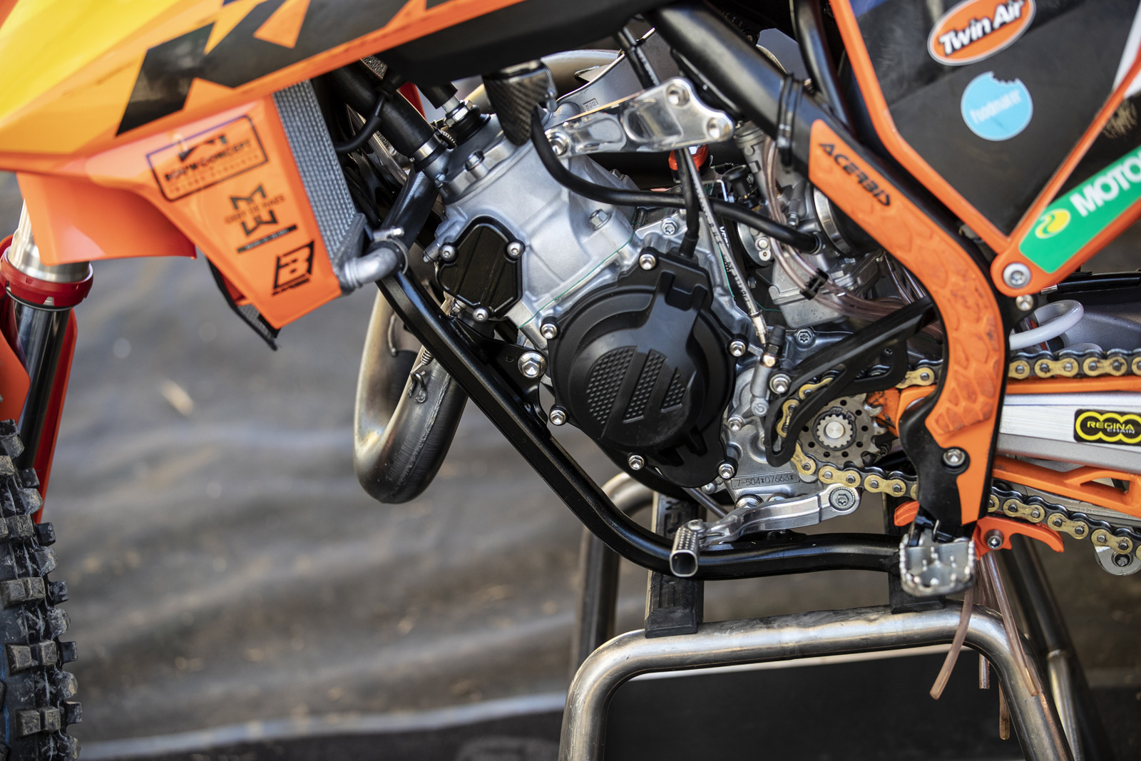 On the other side, you can see another polished engine hanger and a carbon fiber guard for the fuel petcock. Also, the team runs the fuel line behind the clutch line.