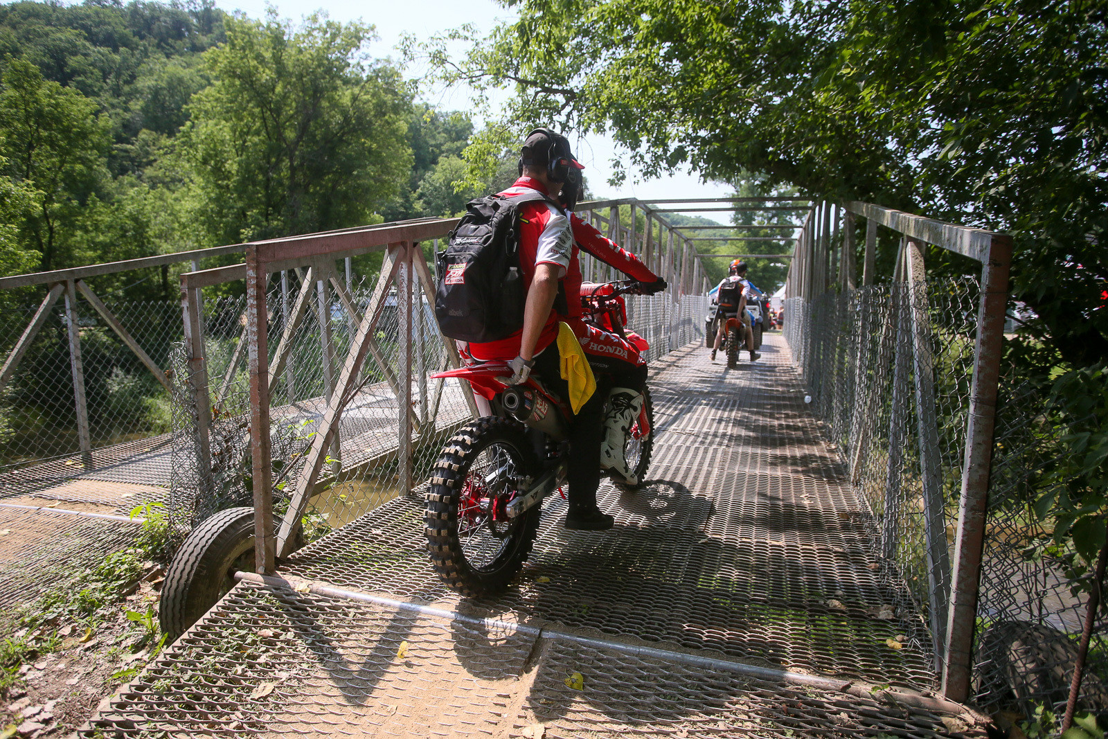 Coty Schock and Tony Archer making the trek across the bridge that spans Spring Creek from the pits to the track.